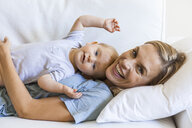 Happy mother cuddling with her baby girl on couch - TCF05864