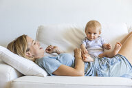 Happy mother lying on couch with her baby girl - TCF05870