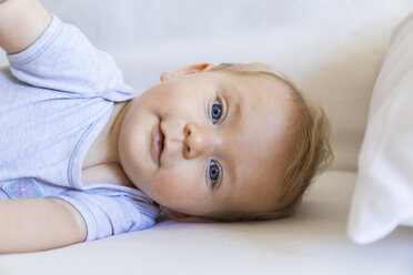Portrait of blond baby girl lying on couch - TCF05876