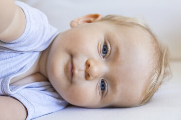 Portrait of blond baby girl lying on couch - TCF05879