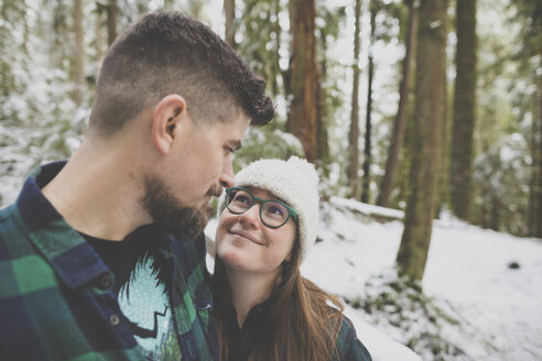 Close-up of loving couple looking each other face to face in forest at Lynn Canyon Park during winter - CAVF49683