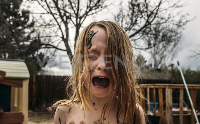 Close-up of girl crying and screaming with mud on face at backyard - CAVF49692