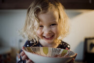 Close-up portrait of happy girl holding bowl at home - CAVF49704