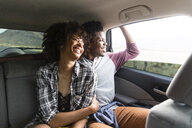 Happy couple looking through window while traveling in car - CAVF49728