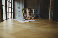 Shirtless baby boy with dirty hands sitting by wooden table at home - CAVF49746