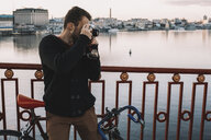 Cyclist photographing with camera while standing with bicycle on bridge over river in city during sunset - CAVF49755