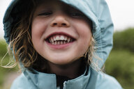 Close-up portrait of cute happy girl in blue raincoat standing against plants during rainy season - CAVF49815