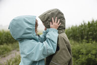 Side view of siblings in raincoats looking at each other while standing against plants during rainy season - CAVF49818