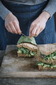 Midsection of woman making sandwich on cutting board at home - CAVF49854