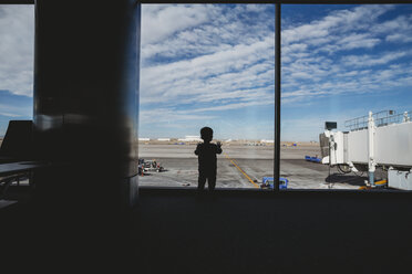 Rear view of silhouette baby boy looking through window at airport departure area - CAVF49866