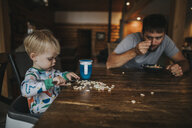 Father with son eating breakfast cereals while sitting at home - CAVF49869