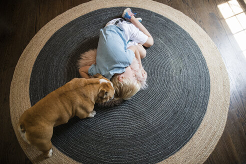 High angle view of pug standing by boy sleeping on carpet at home - CAVF49884