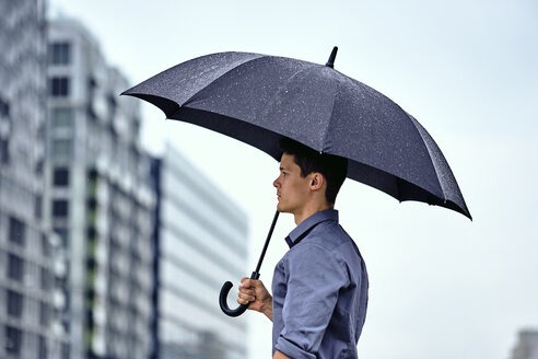 Side view of young businessman with umbrella standing against buildings and sky in city during rainfall - CAVF49896