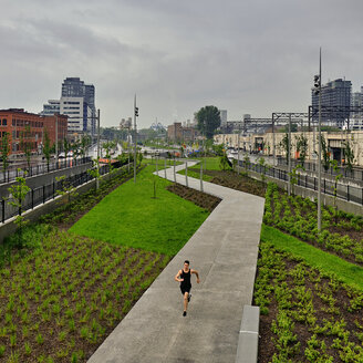 High angle view of young man running on footpath at park in city during rainy season - CAVF49899