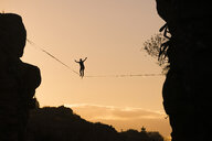 Low angle view of silhouette man slacklining against sky during sunset - CAVF49902