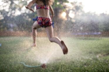 Low section of girl in swimwear running on grassy field at yard - CAVF49905