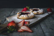 Tarts with strawberry slices on wooden table against black background - CAVF49908