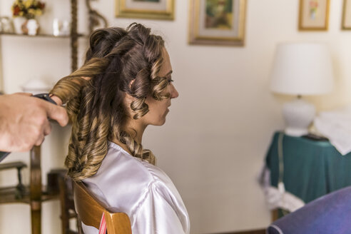 Cropped hands of hairdresser using curlers on bride's hair at home - CAVF49914