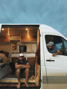 Man looking at thoughtful friend through window while sitting in motor home against cloudy sky - CAVF49917