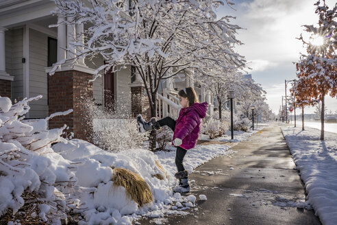Side view of playful girl kicking snow on road against cloudy sky - CAVF49926