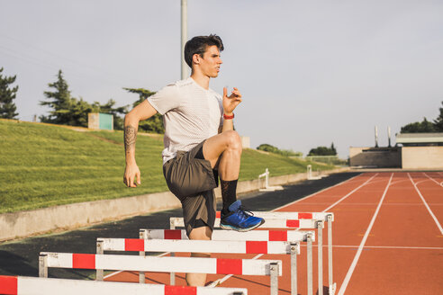 Athlete doing warm-up exercises on a tartan track for a hurdle race - ACPF00351