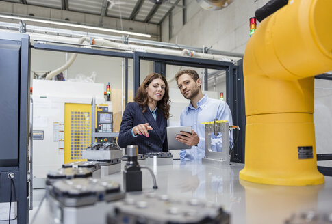 Colleagues in high tech company controlling industrial robots, using digital tablet - DIGF05145