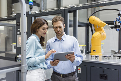 Colleagues in high tech company controlling industrial robots, using digital tablet - DIGF05154