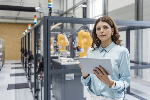 Businesswoman in high tech company controlling industrial robots, using digital tablet - DIGF05163