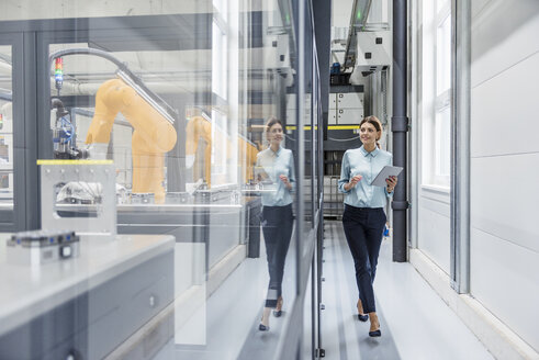 Businesswoman checking robots with digital tablet in high tech company - DIGF05181
