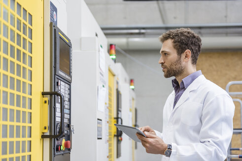 Employee checking manufacturing machines in high tech company, using digital tablet - DIGF05217