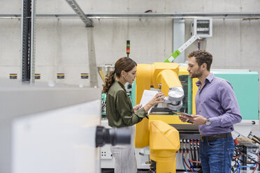 Businessman and woman having a meeting in front of industrial robots in a high tech company - DIGF05226