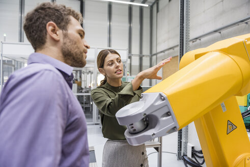 Businessman and woman having a meeting in front of industrial robots in a high tech company - DIGF05229