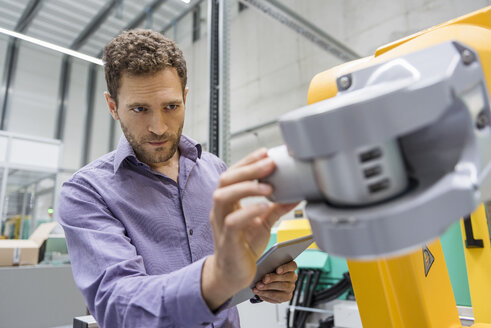 Technician adjusting industrial robot - DIGF05232