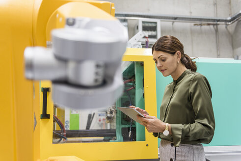 Businesswoman checking industrial robot in high tech company - DIGF05235