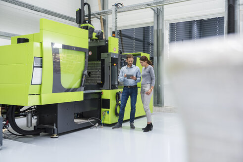 Colleagues in high tech company controlling manufacturing machines, using digital tablet - DIGF05247