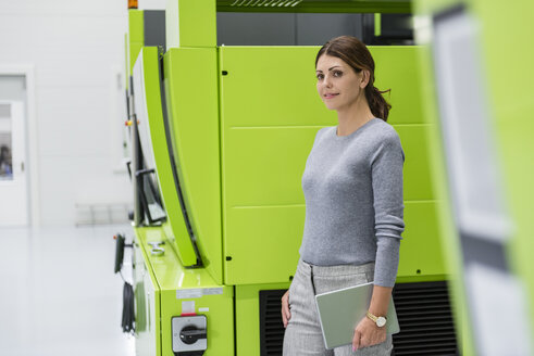 Businesswoman in high tech company controlling manufacturing machines - DIGF05250