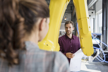 Businessman and woman having a meeting in front of industrial robots in a high tech company - DIGF05256