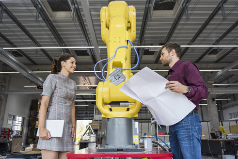 Businessman and woman having a meeting in front of industrial robots in a high tech company - DIGF05259
