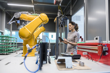 Businesswoman checking industrial robot in high tech company - DIGF05262