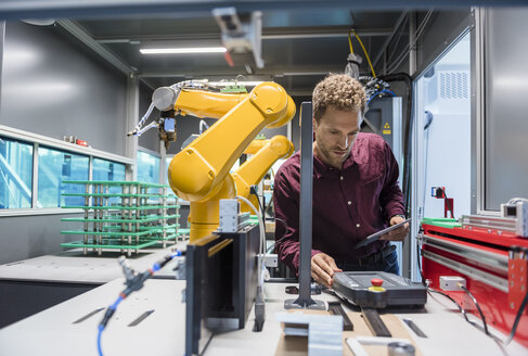 Businessman checking industrial robot in high tech company - DIGF05265