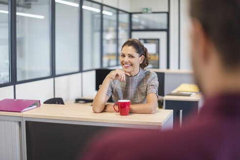 Female employee sitting at desk, talking to colleague - DIGF05271