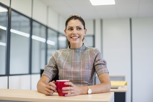 Pretty office worker sitting at desk with red coffee cup - DIGF05274