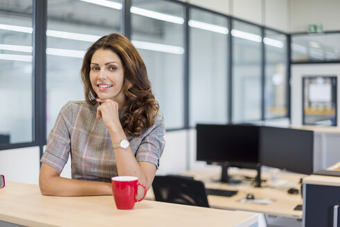 Pretty office worker sitting at desk with red coffee cup - DIGF05277