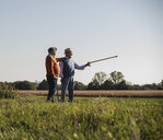 Two old friends standing in the fields, pointing with walking stick - UUF15456