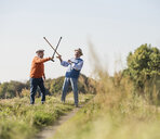 Two old friends fencing in the fields with their walking sticks - UUF15471