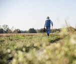 Senior man carrying traveling bag, walking in the fields - UUF15474