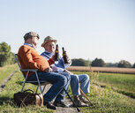 Two old friends sitting in the fields, drinking beer, talking about old times - UUF15477