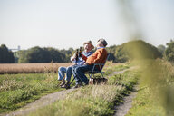 Two old friends sitting in the fields, drinking beer, talking about old times - UUF15480