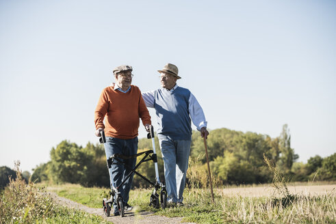 Old friends taking a stroll in the fields with walking stick and wheeled walker, talking about old times - UUF15489