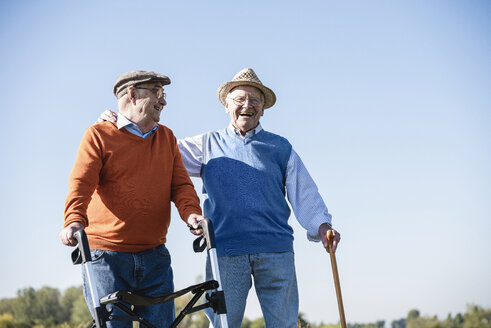 Old friends taking a stroll in the fields with walking stick and wheeled walker, talking about old times - UUF15492